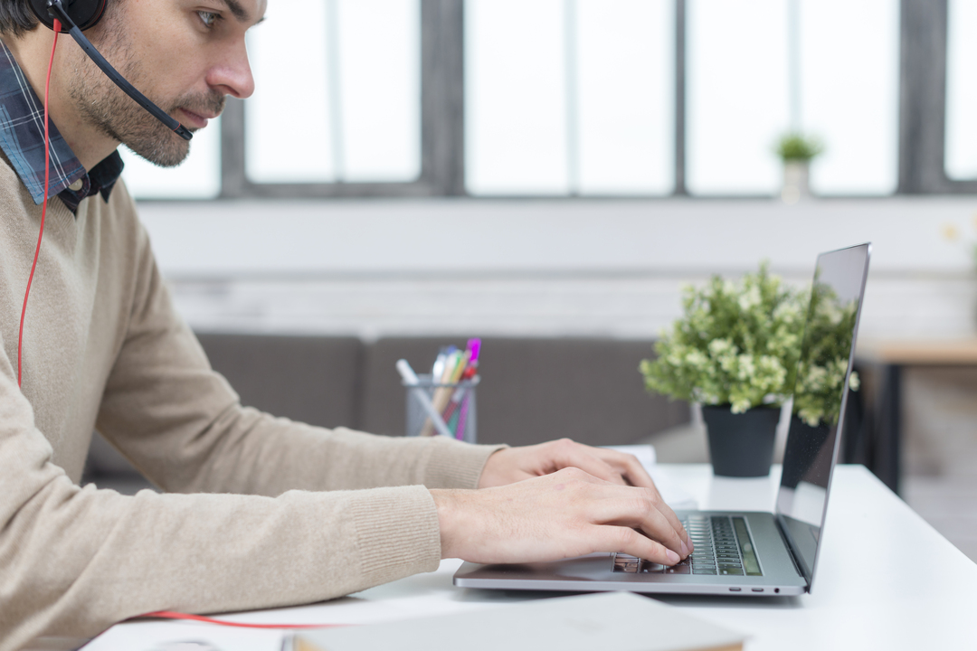 homem sentado digitando no computador, usando fones de ouvido, em atendimento remoto