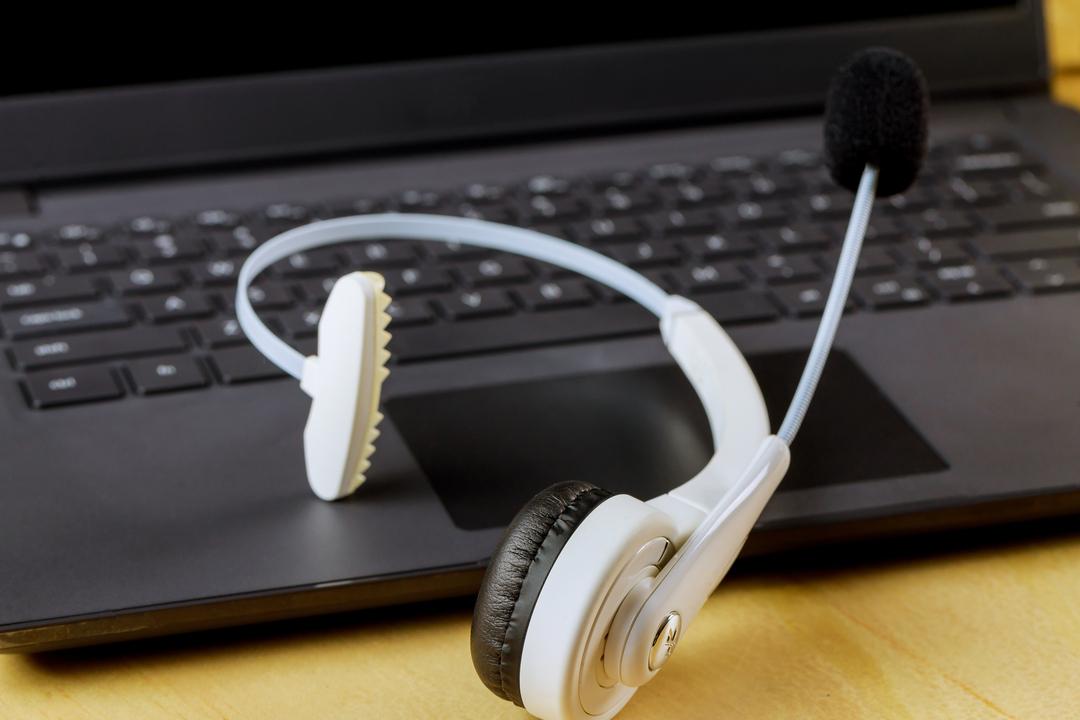 Telefonia ip e voip: Imagem fechada mostra fone de ouvido, estilo telemarketing, colocado sobre teclado de notebook