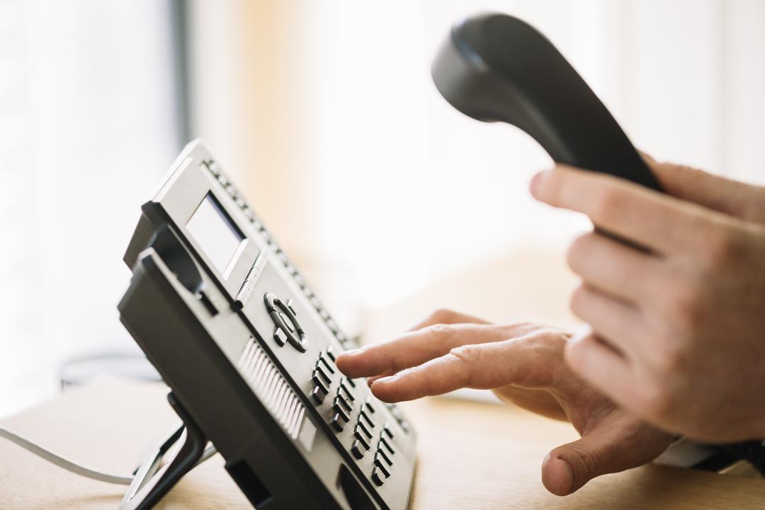 Serviços de telefonia: imagem fechada mostra uma mão segurando telefone digitando os números