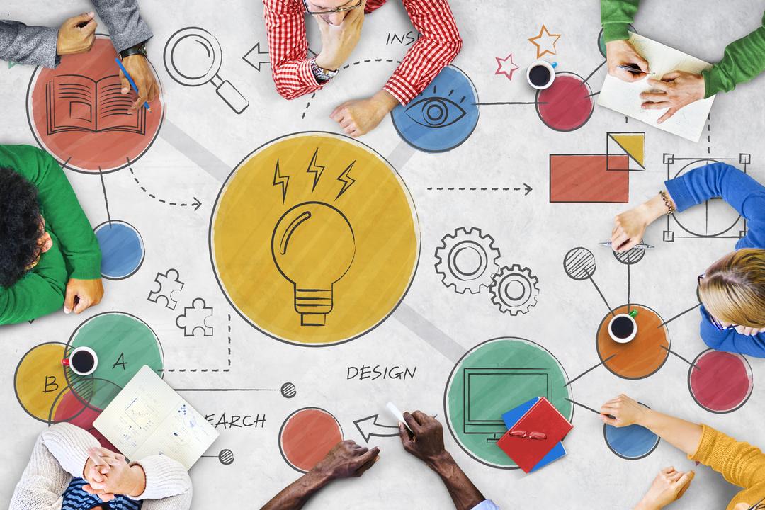 Roda de pessoas em volta de uma mesa, desenhando juntas diversas soluções e ideias, exemplificando assim, como funciona a comunicação integrada.