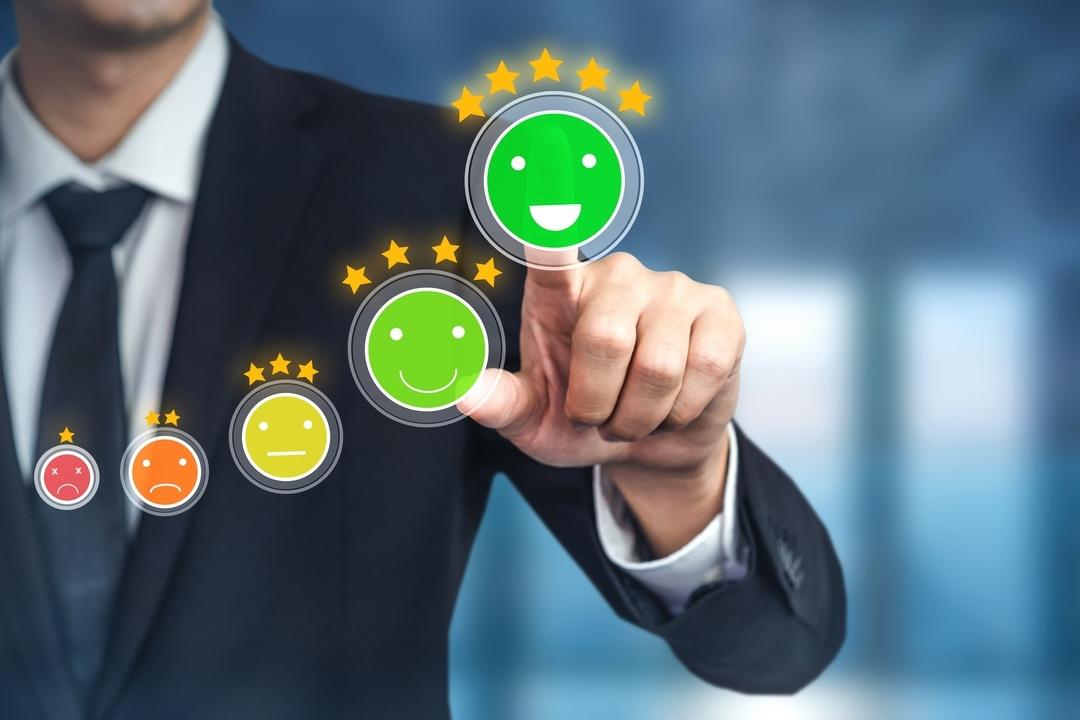 Experiência do cliente: na imagem, existem cinco emojis de carinha feliz e triste, com cores as cores vermelha, laranja, amarela e verde, representando assim a satisfação do cliente. Atrás, homem executivo aponta para a opção de emoji mais feliz.
