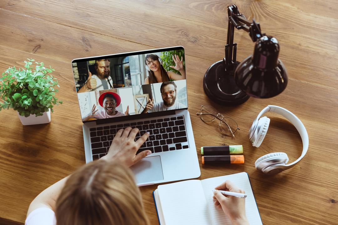 Imagem de cima mostra mulher em vídeo chamada com colegas no computador, em escritórios virtuais.