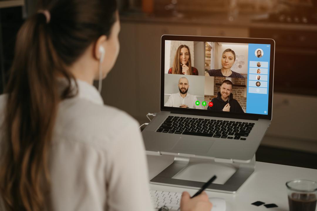 A imagem mostra uma mulher em frente ao notebook fazendo a gestão de equipes remotas, onde na tela é possível ver o rosto de quatro pessoas fazendo parte da reunião.