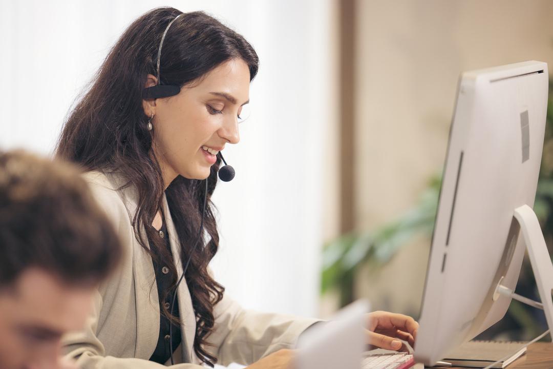 Na imagem tem uma mulher realizando tipos de atendimento ao cliente, onde ela está com um fone com microfone de frente para um computador.